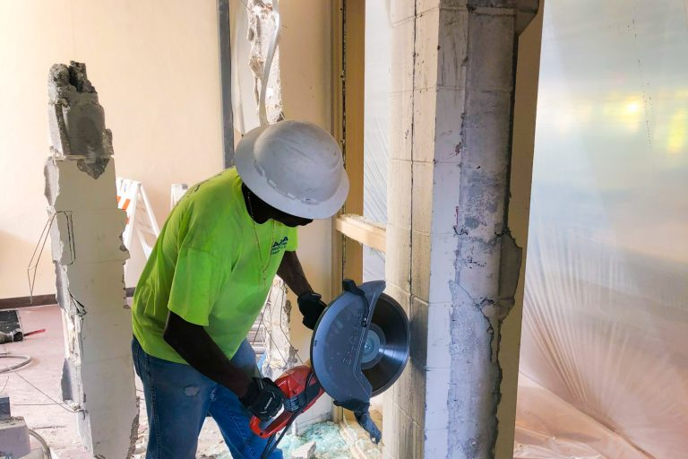 worker with concrete saw cutting wall interior demolition